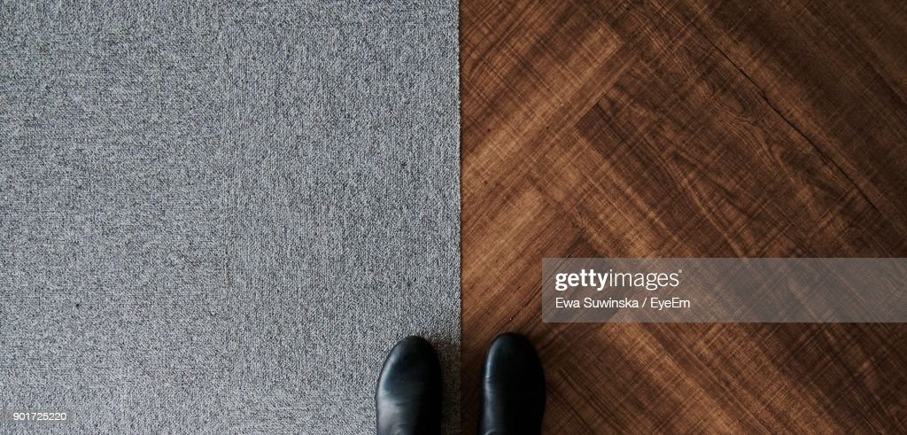 Low Section Of Person Standing On Hardwood Floor And Carpet : Stock Photo