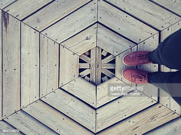 Low Section Of Person Standing On Hexagon Shape Wooden Floor