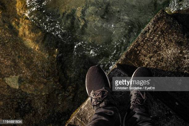 low section of person standing on retaining wall by lake - christian soldatke stock pictures, royalty-free photos & images