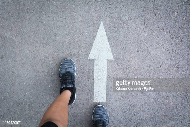 low section of person standing on road - following arrows stock pictures, royalty-free photos & images