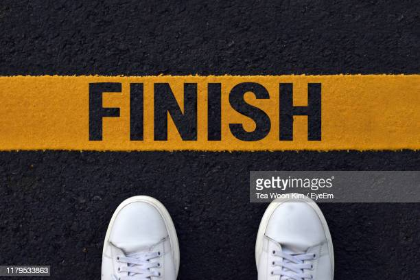 low section of person standing on road with text finish - finishing line stock pictures, royalty-free photos & images