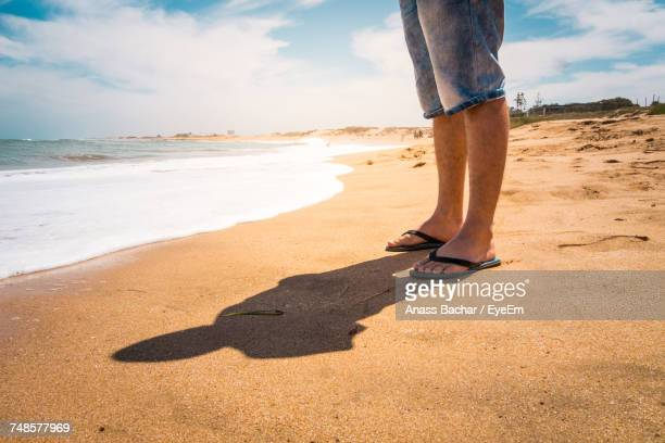 low section of person standing on sand at beach - gold sandals stock pictures, royalty-free photos & images