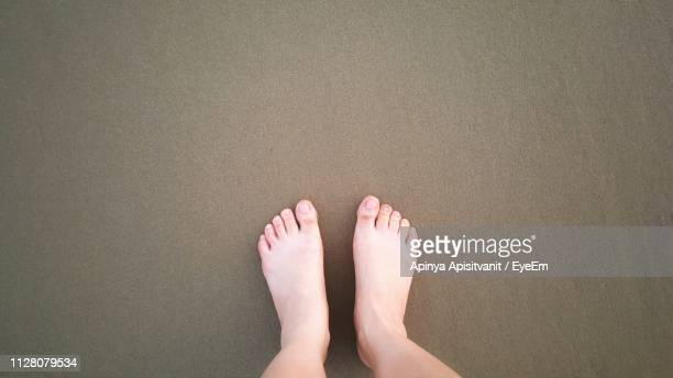 low section of person standing on sand - barefoot stock pictures, royalty-free photos & images