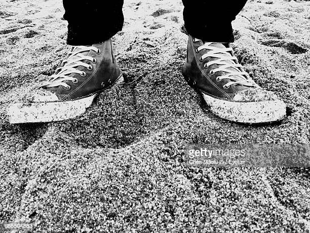 low section of person standing on sand - boao economic forum stock pictures, royalty-free photos & images