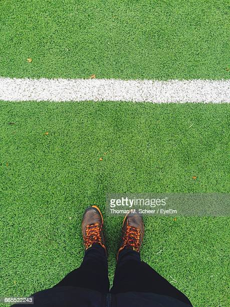 Low Section Of Person Standing On Soccer Field