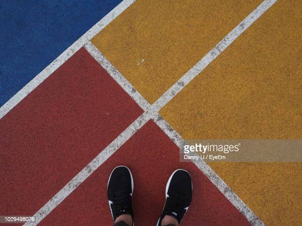 low section of person standing on sports track - sezione inferiore foto e immagini stock