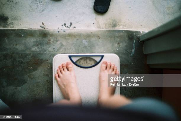 low section of person standing on weight scale - human foot stock pictures, royalty-free photos & images