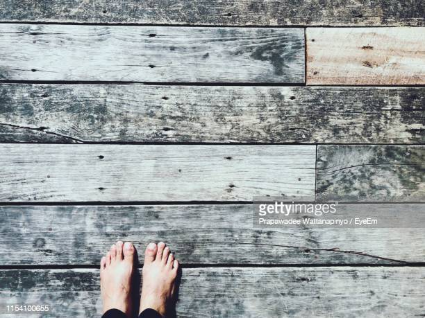 low section of person standing on wood - floorboard stock photos and pictures