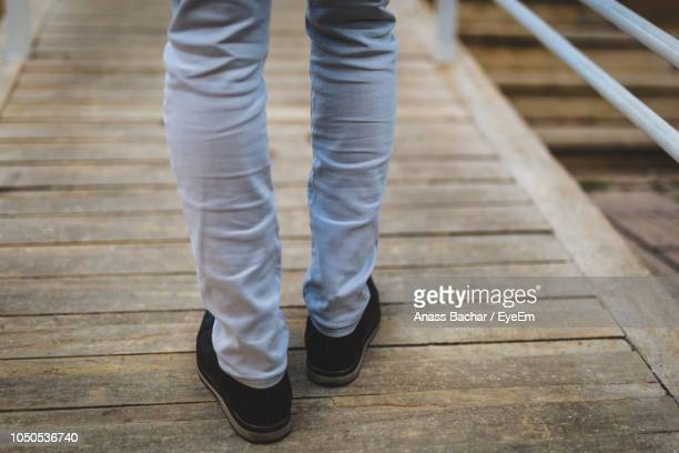 Low Section Of Person Standing On Wooden Bridge
