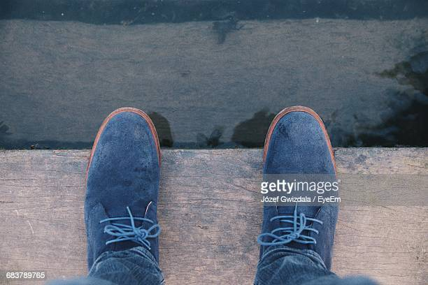 low section of person standing on wooden plank by the water - blue shoe stock pictures, royalty-free photos & images