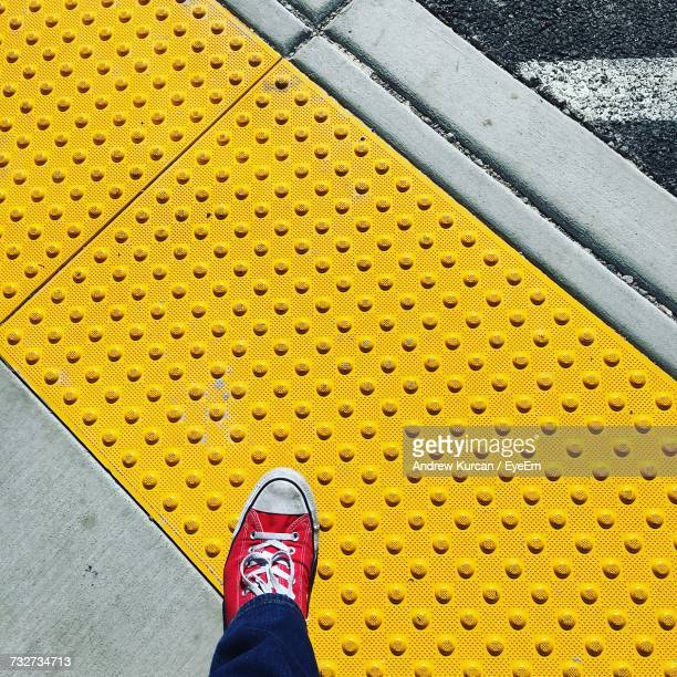 Low Section Of Person Standing On Yellow Floor