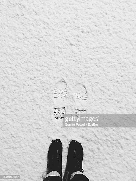Low Section Of Person Standing With Footprint On Snow