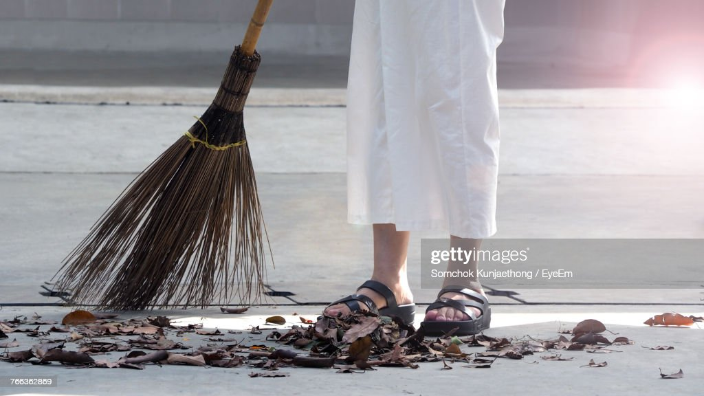 Low Section Of Person Sweeping Leaves On Street : ストックフォト