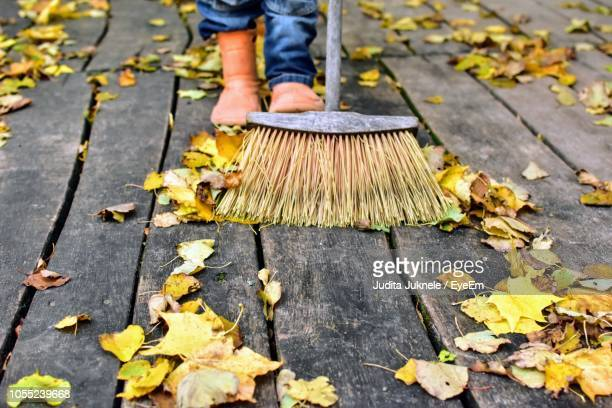 low section of person sweeping on boardwalk - sweeping stock pictures, royalty-free photos & images