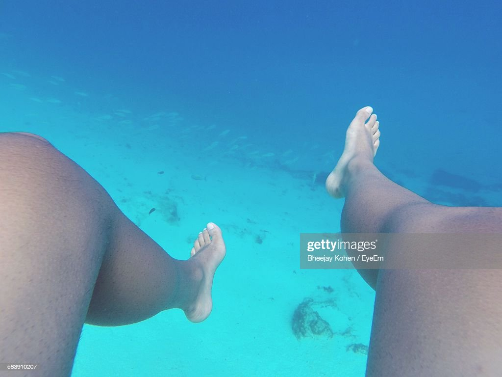 Low Section Of Person Swimming In Sea : Stock Photo