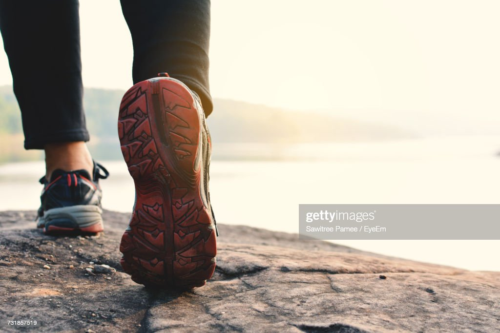 Low Section Of Person Walking At Lakeshore : Stock Photo