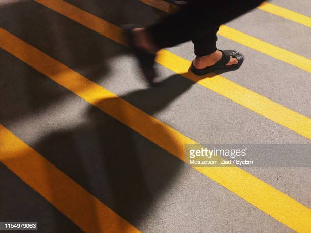low section of person walking on crosswalk in city - riyadh stock pictures, royalty-free photos & images