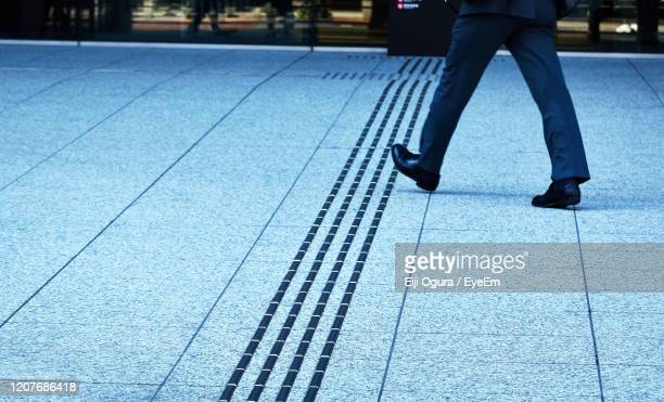 low section of person walking on footpath - 人の足 ストックフォトと画像