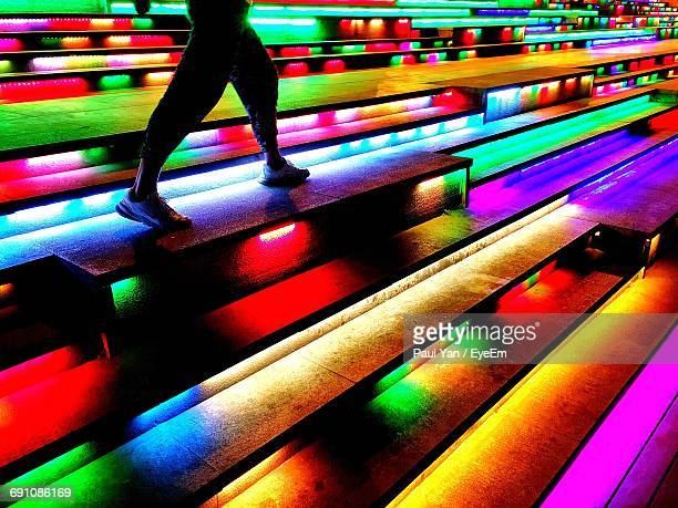 low section of person walking on multi colored illuminated stairs - steps stock photos and pictures