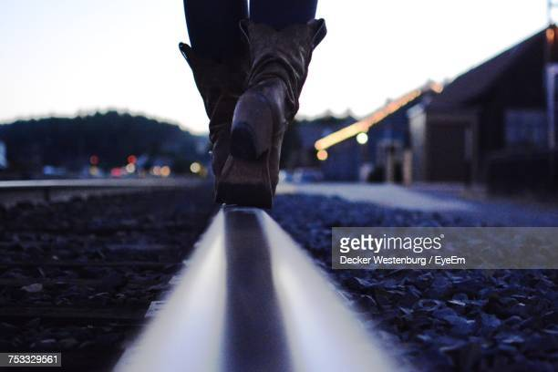 low section of person walking on railroad track at dusk - カウボーイブーツ ストックフォトと画像