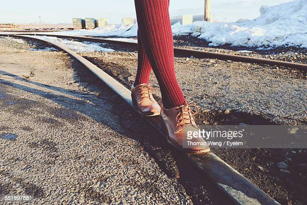 low section of person walking on railroad track - stepping stock pictures, royalty-free photos & images