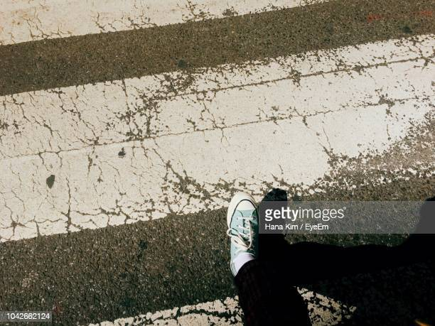 low section of person walking on road - 人の足 ストックフォトと画像