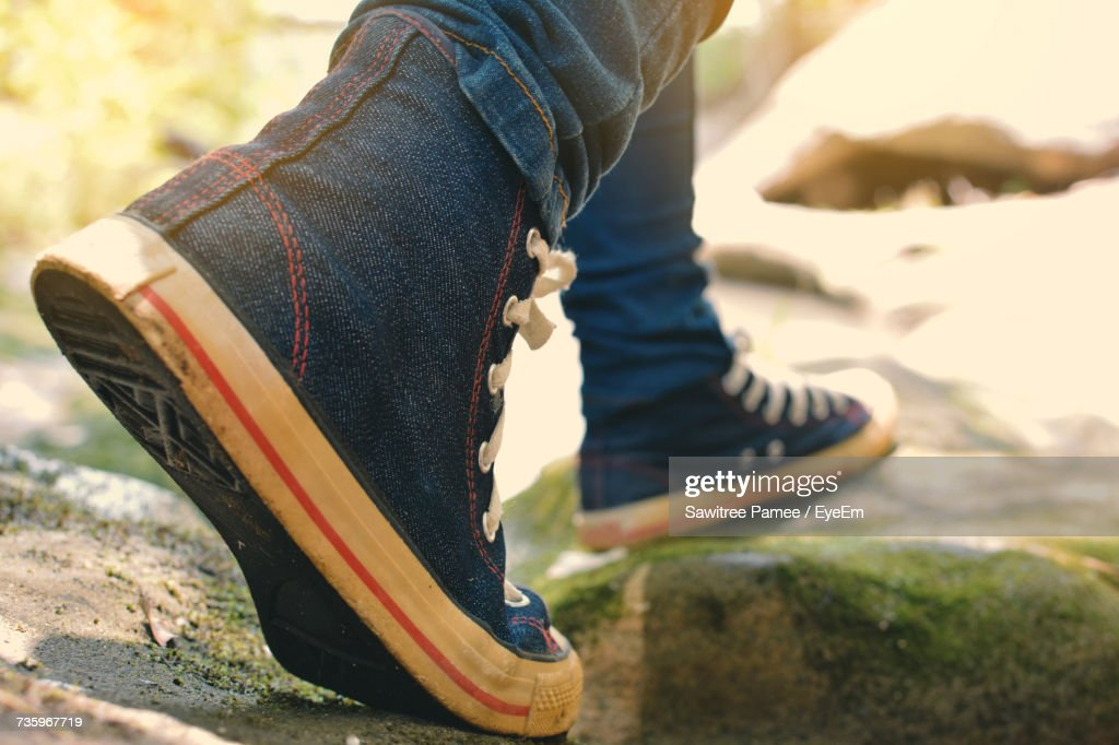 Low Section Of Person Walking Outdoors On Sunny Day : Stock Photo