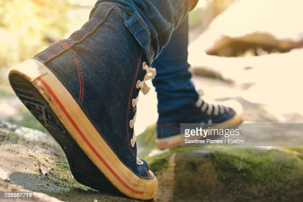 low section of person walking outdoors on sunny day - 靴底 ストックフォトと画像