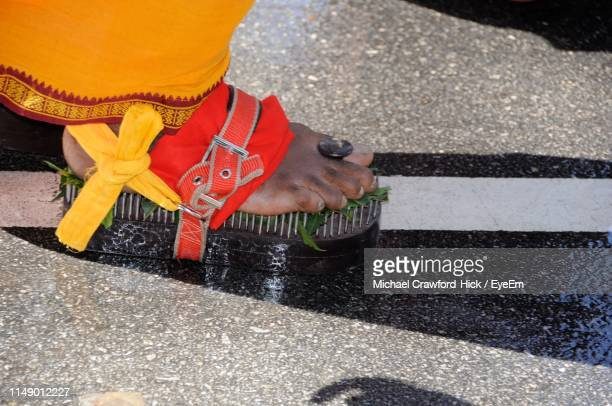 low section of person walking while wearing shoe with nails on road - menselijk lichaamsdeel stockfoto's en -beelden