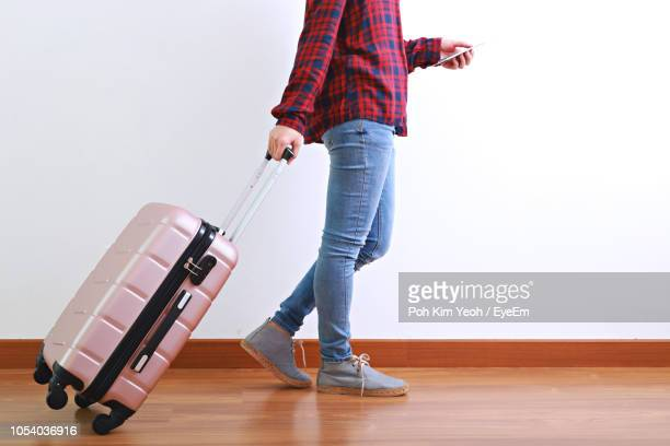 Low Section Of Person Walking With Suitcase Against White Wall