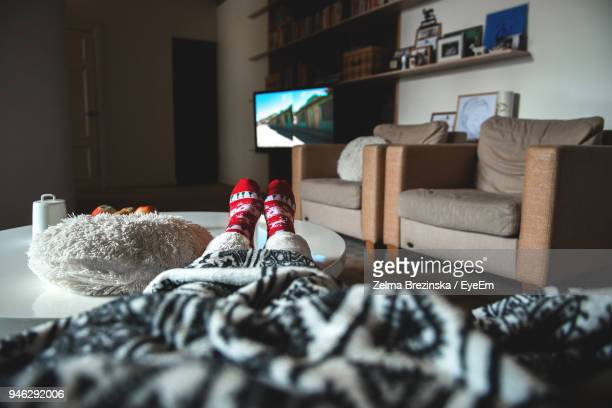 low section of person watching tv at home - partie inférieure photos et images de collection