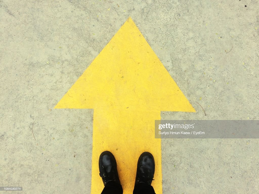 Low Section Of Person Wearing Black Shoes Standing On Yellow Arrow Symbol : Stock Photo