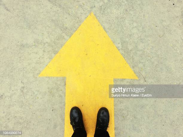 low section of person wearing black shoes standing on yellow arrow symbol - symbol stock pictures, royalty-free photos & images