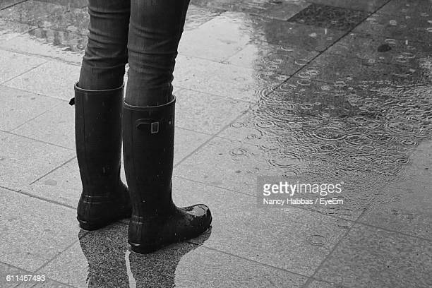 low section of person wearing boots while standing on street during monsoon - rainy season stock pictures, royalty-free photos & images