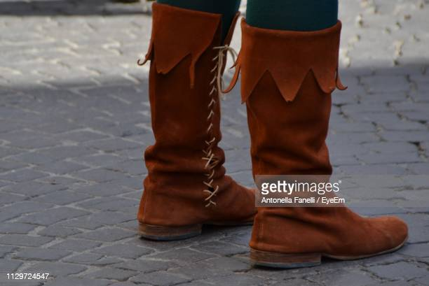 Low Section Of Person Wearing Boots While Standing Outdoors