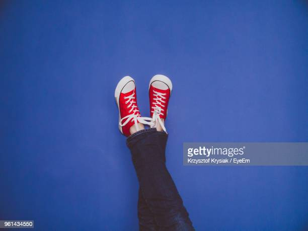low section of person wearing canvas shoes by blue wall - feet up stock pictures, royalty-free photos & images