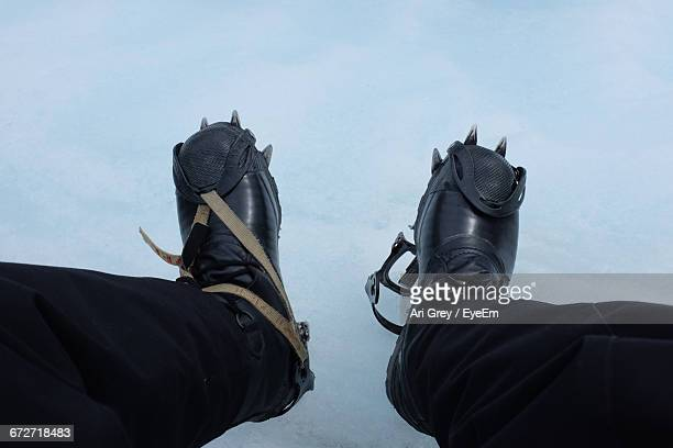 Low Section Of Person Wearing Crampon Shoes On Snow Covered Field