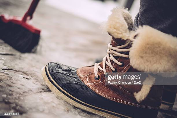 Low Section Of Person Wearing Fur Boot During Winter