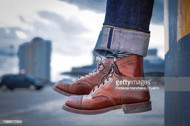 low section of person wearing leather shoes in city - calzature di pelle foto e immagini stock