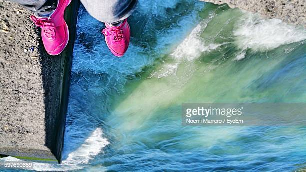 low section of person wearing pink shoes standing over sea - noemi foto e immagini stock