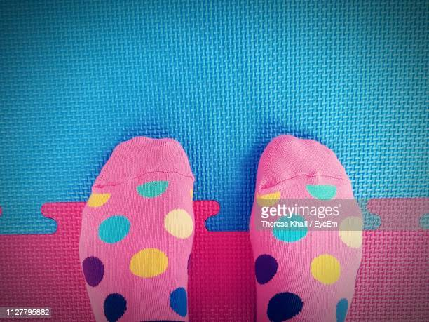 low section of person wearing pink socks while standing on mat - pink sock image stock pictures, royalty-free photos & images