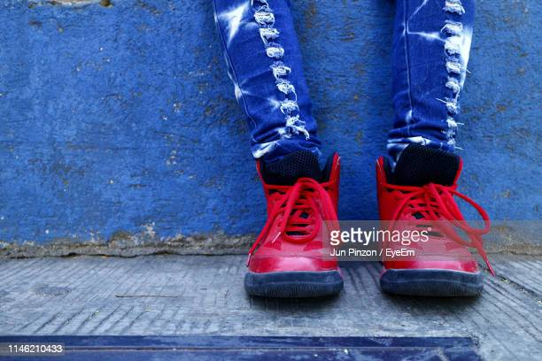 low section of person wearing red shoes while standing on footpath - pair stock pictures, royalty-free photos & images