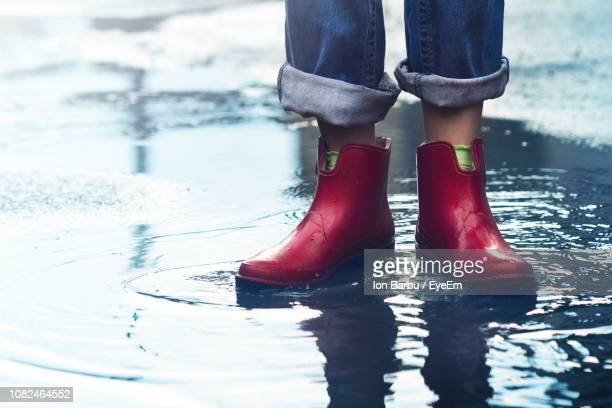 Low Section Of Person Wearing Rubber Boots While Standing In Puddle