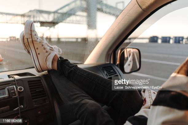 low section of person wearing shoes in car - legs crossed at ankle stock pictures, royalty-free photos & images