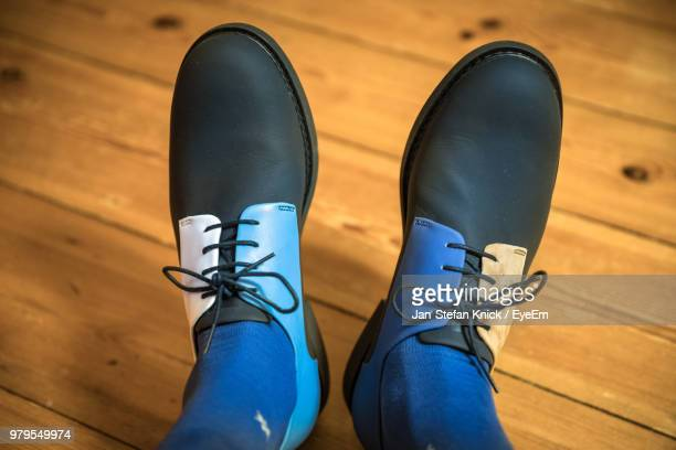 Low Section Of Person Wearing Shoes On Hardwood Floor