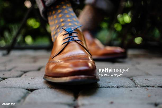 low section of person wearing shoes - brown shoe stock photos and pictures