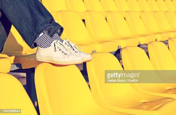 low section of person wearing shoes sitting on chair in stadium - yellow shoe stock pictures, royalty-free photos & images