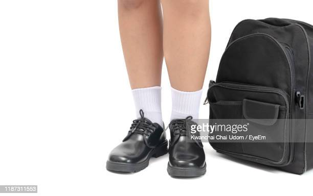 low section of person wearing shoes standing by bag against white background - black shoe stock pictures, royalty-free photos & images