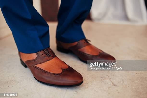 low section of person wearing shoes standing on tiled floor - lino stock pictures, royalty-free photos & images