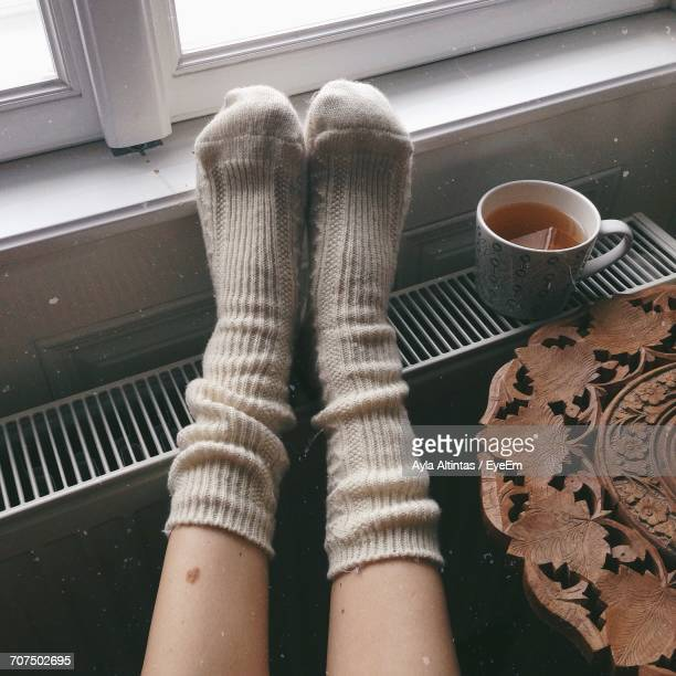 low section of person wearing socks by tea cup on radiator at home - radiator heater stock photos and pictures